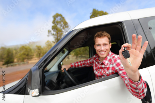 Man driving rental car showing car keys happy