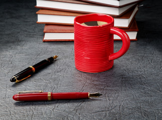 Pens with a cup of coffee and organizers