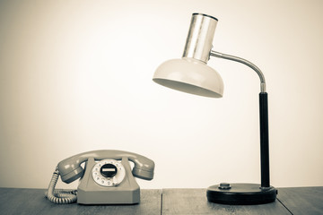 Retro telephone and desk lamp on table