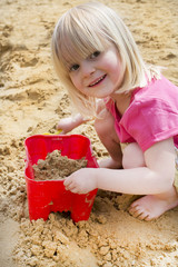 little girl on sandy beach with bucket and spade