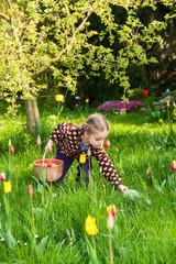 Kleines Mädchen sucht Ostereier auf einer Blumenwiese