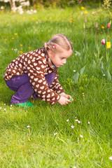 Kleines Mädchen mit Zöpfen sucht Ostereier