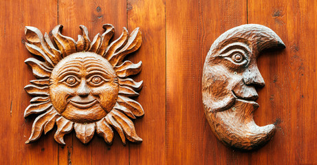 Ancient door with Moon and Sun face carved from wood