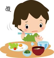 食事中に野菜を残す男の子