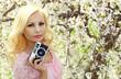 Blonde Girl with Retro Camera over Cherry Blossom. Beautiful