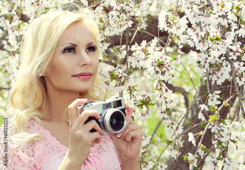 Blonde Girl with Retro Camera over Sakura. Beautiful Young Woman