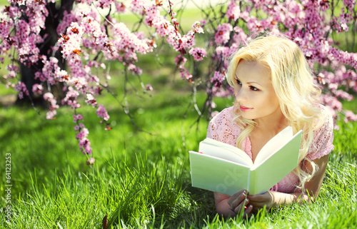 Girl reading the Book under Cherry Blossom. Blonde young woman