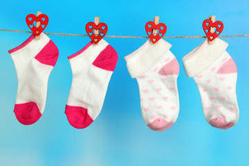 Socks hanging on clothesline on bright background