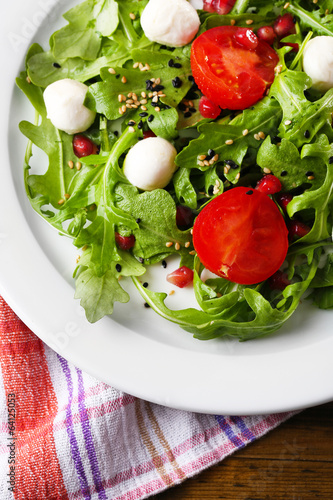 Green salad made with  arugula, tomatoes, cheese mozzarella