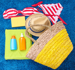 Wicker bag, swimsuit, bottles with lotions on color background.
