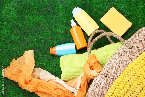 Wicker bag with colorful scarf, towel, bottles of lotions