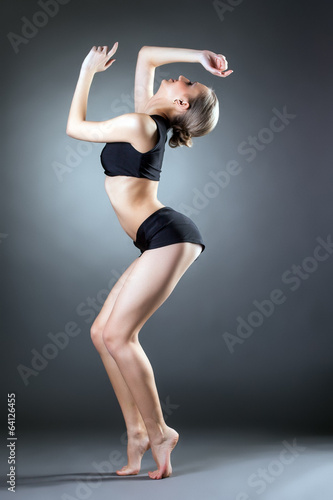 Slender young girl practicing gymnastics in studio