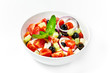 Light greek salad with fresh vegetables, garnished with basil.