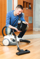 Young man cleaning vacuum cleaner