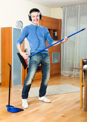 Happy young  guy  with dustpan and brush