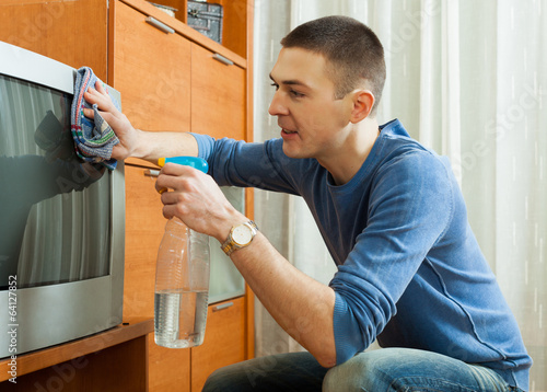 man cleaning TV