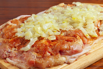 raw chicken piece with spices and onions