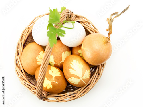 Wicker basket with colored eggs onion and parsley  isolated