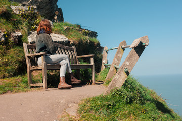 Woman sitting on bench atop a cliff