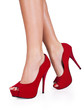 Woman legs wearing red high heels isolated on white background.