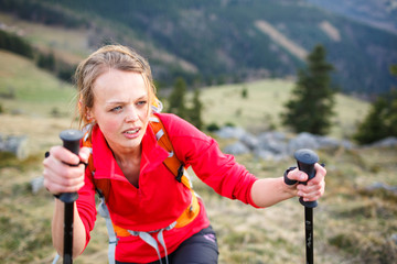 Pretty, young female hiker having a tough walk uphill