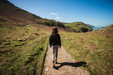 Woman walking along path in the mountains