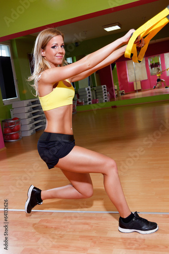 Beautiful young woman doing exercises in the gym