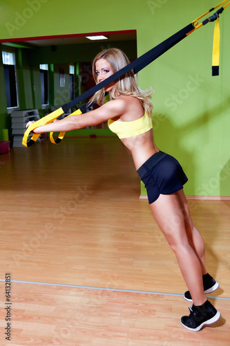 Beautiful young woman doing TRX exercises in the gym