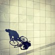 canvas print picture - Cycling man and his shadow in Berlin