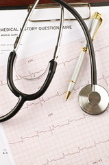 Stethoscope and pen over medical questionnaire and cardiogram
