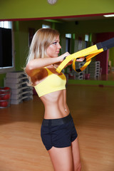 Beautiful young woman illustrating TRX exercise in the gym
