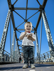 Boy with phone on the bridge in the city of skyscrapers