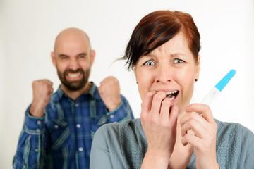 Jubelnder Mann und ängstliche Frau mit Schwangerschaftstest
