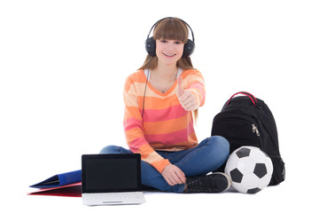 sitting teenage girl listening music in headphones with laptop