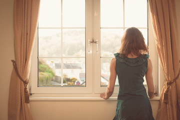 Young woman in dress looking out the window