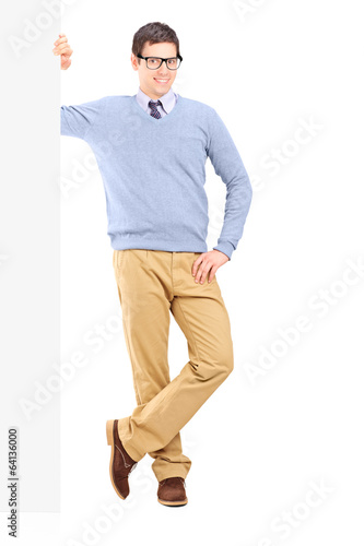 Casual man leaning on a blank panel