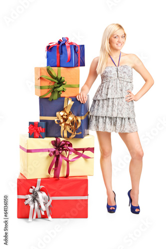 Woman standing next to a stack of presents