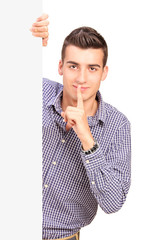 Man holding finger on lips behind blank panel