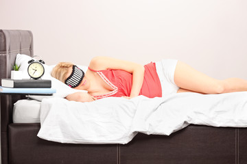 Woman sleeping with eye mask in a bedroom