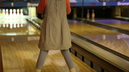 bowling - a little girl knocks down pins and very glad