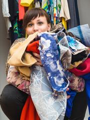 Девушка с охапкой одежды в руках