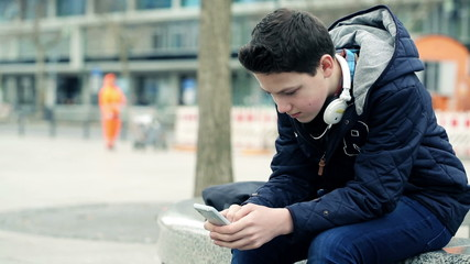 Young teenager texting, sending sms on smartphone in the city