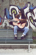 Girl sitting on a bench and playing guitar
