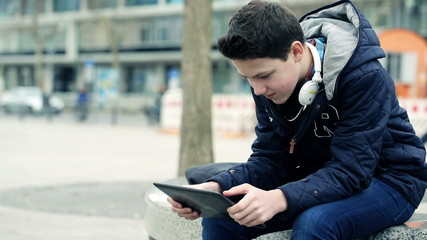 Young teenager with tablet computer in the city