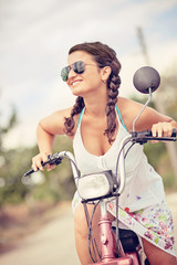 young smiling woman on scooter with sunglasses and braid hair