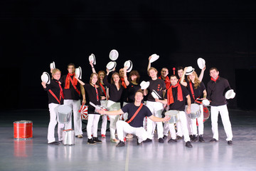 Music group of drummers in costumes with hats raised