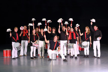 Orchestra drummers with hats raised on drumsticks