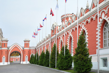 Flagpoles along wall with pointed windows of Petroff Palace