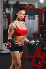 Perfect bodybuilding fitness body girl with barbell in the gym