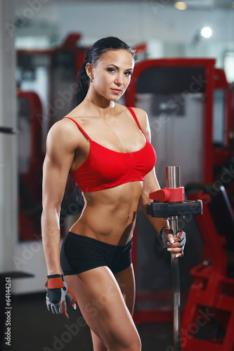 fitness body girl with barbell in the gym